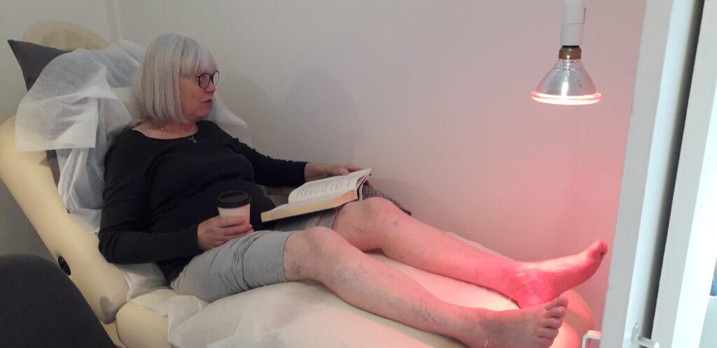 En dame der sidder i akupunktur stol, midt behandling - Akupunkturbehandling