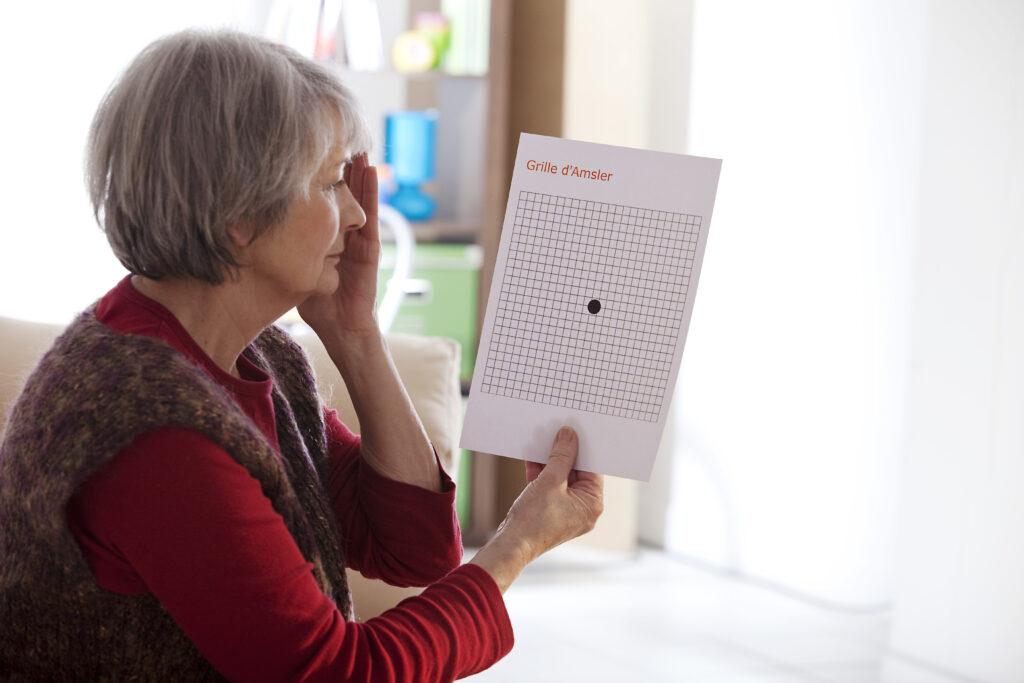 En dame der holder hendes venstre hånd over sit øje og kigger på en øje test - AMD