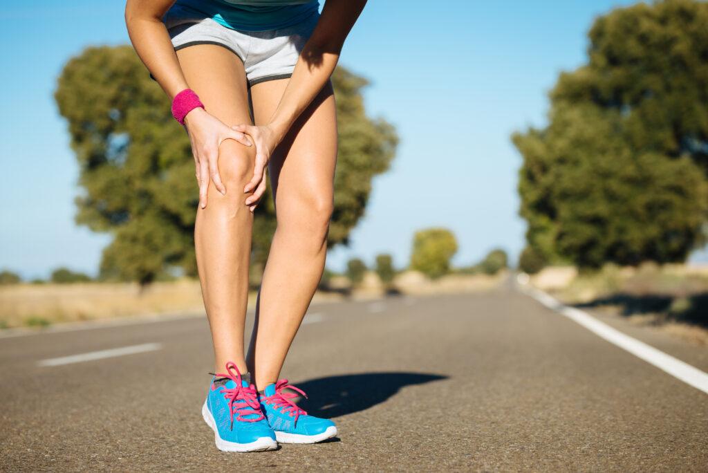 En person der løber på en vej, som har ondt i sin højre knæ - Knæsmerter