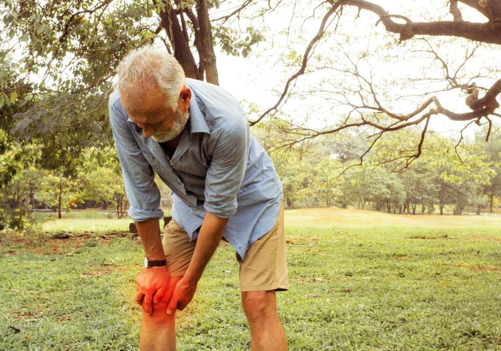 En gammel mand med sin højre knæ der gør ondt - Slidgigt - artrose