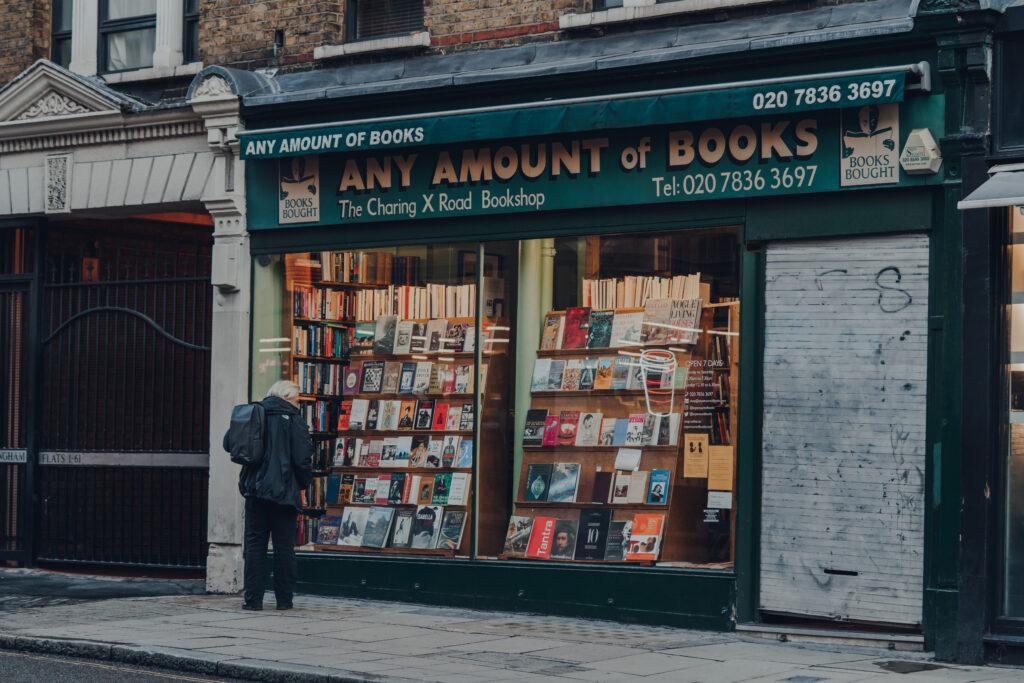Et billede af en gammel mand der står stille foran et bog butik - Vindueskiggerben