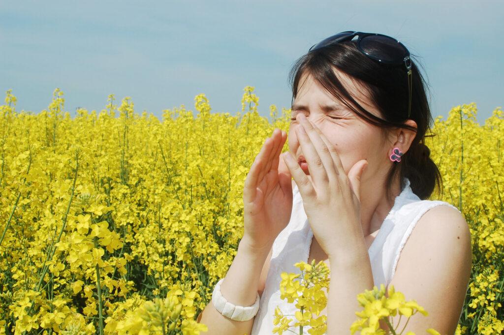 En person der nyser og har allergi i en blomstermark - Allergi